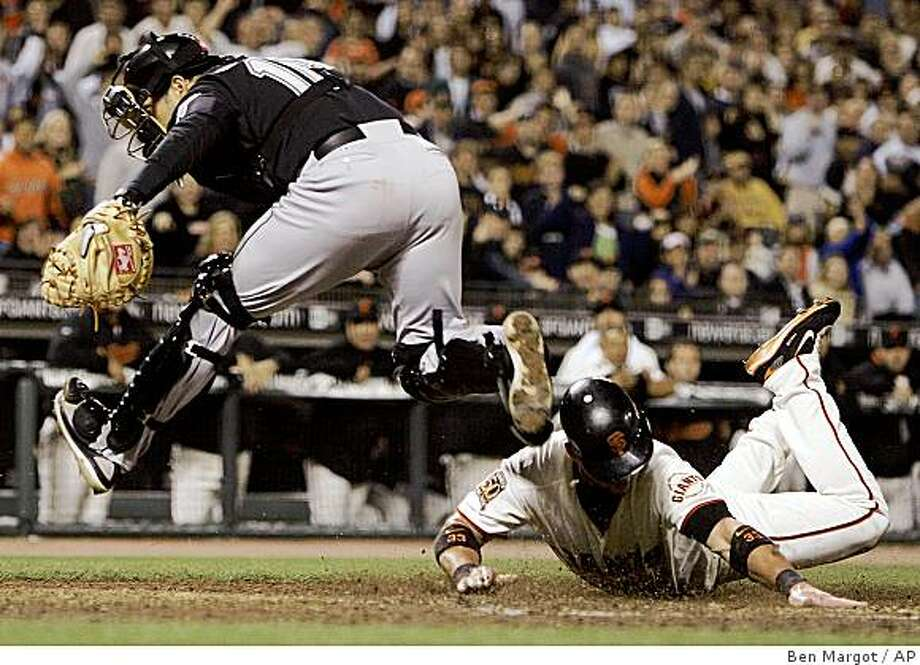 Florida Marlins catcher Paul Lo Duca, left, chases the ball as San Francisco Giants' Aaron Rowand scores during the sixth inning of a baseball game Wednesday, Aug. 20, 2008, in San Francisco. (AP Photo/Ben Margot) Photo: Ben Margot, AP