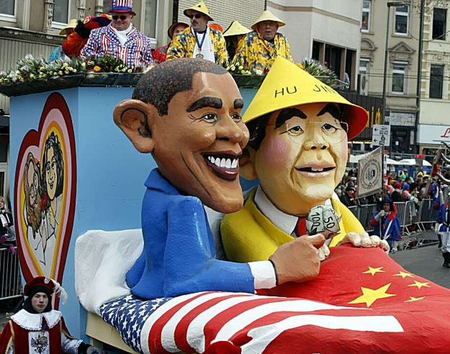 Effigies of US President Barack Obama and Chinese Prime Minister Hu Jintao are seen sitting together in a bed on a float, during the Carnival Rose Monday Parade in Cologne, Germany, Monday Feb. 15, 2010. The float satirically illustrates the ties betweenthe USA and China. Photo: Roberto Pfeil, AP