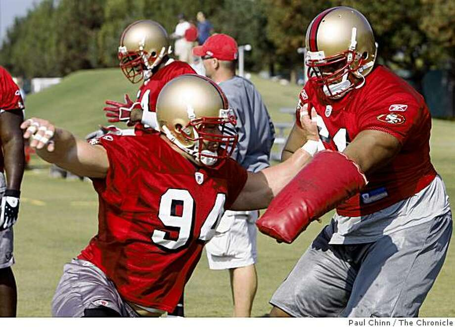 Defensive lineman Justin Smith (left) works on a drill with LaJuan Ramsey  during training camp for the San Francisco 49ers in Santa Clara, Calif., on Friday, July 25, 2008. Photo: Paul Chinn, The Chronicle