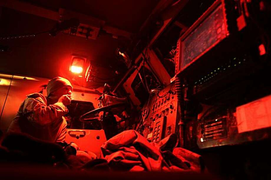 A US army soldier with Task Force Thorn sits in his MRAP at night in Trikh Nawar on the northeastern outskirts of Marjah on February 22, 2010. A NATO air strike killed up to 27 Afghan civilians, including women and a child, sparking fresh anger from Kabulagainst US-led forces pressing a major offensive to defeat the Taliban. Photo: Patrick Baz, AFP/Getty Images