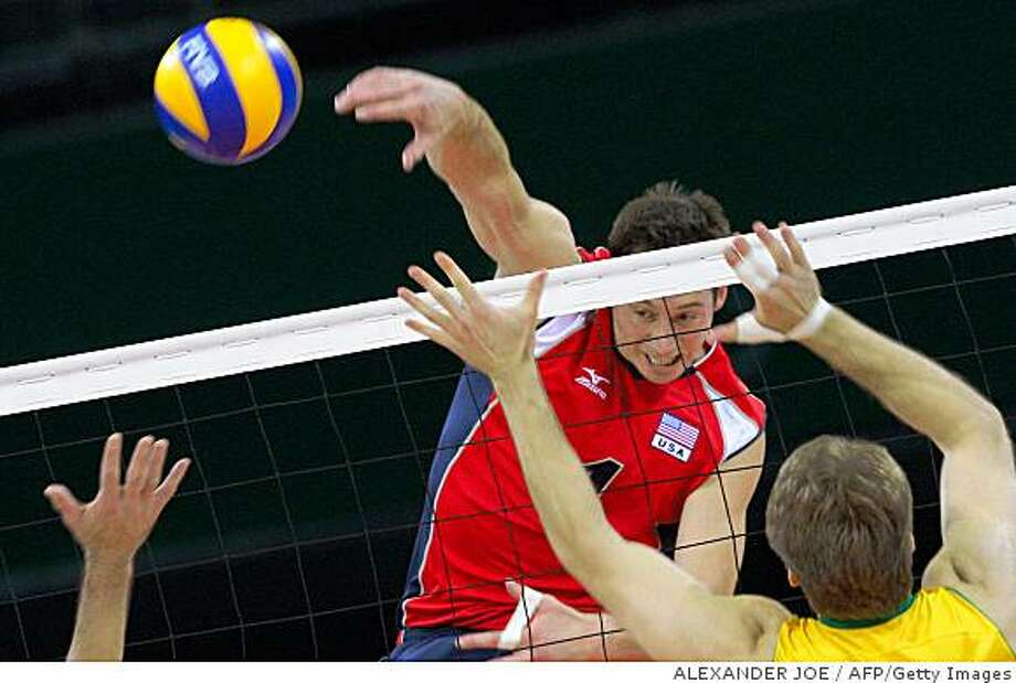 US player David Lee (C) spikes the ball as Brazil's players attempt to block during the men's volleyball gold medal match in the 2008 Beijing Olympic Games in Beijing on August 24, 2008.     AFP PHOTO / ALEXANDER JOE (Photo credit should read ALEXANDER JOE/AFP/Getty Images) Photo: ALEXANDER JOE, AFP/Getty Images