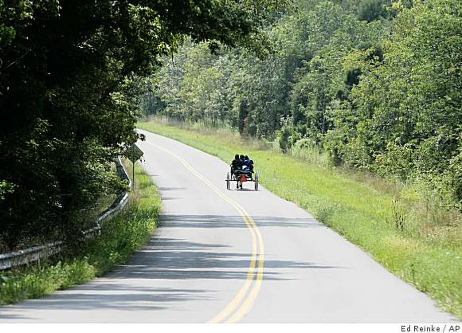 ** ADDS KENTUCKY POPULATION FIGURES **A group of Amish ladies and children make their way home along a winding road near English, Ky., Wednesday, Aug. 20, 2008.  The Amish are expanding their presence in states far beyond Pennsylvania Dutch country as they search for affordable farmland to accommodate a population that has nearly doubled in the past 16 years.  Kentucky's Amish population jumped 200 percent, from 2,835 to 8,505, over the past 16 years.   (AP Photo/Ed Reinke) Photo: Ed Reinke, AP