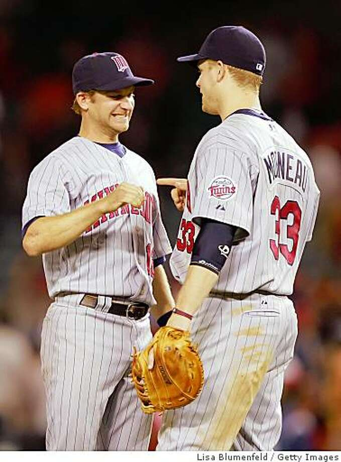 ANAHEIM, CA - AUGUST 21:   (L-R) Adam Everett #12 and Justin Morneau #33 of the Minnesota Twins celebrate defeating the Los Angeles Angels of Anaheim 2-1 in 12 innings at Angels Stadium on August 21, 2008 in Anaheim, California.  (Photo by Lisa Blumenfeld/Getty Images) Photo: Getty Images