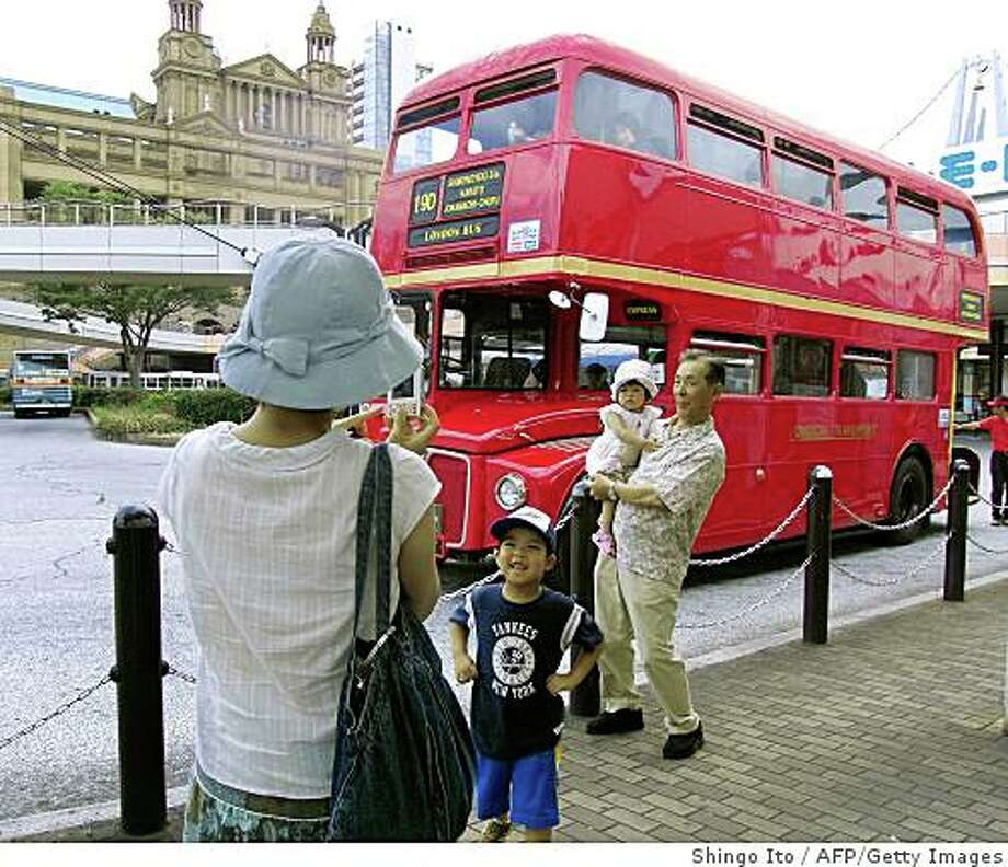 """TO GO WITH STORY BY SHINGO ITO 'JAPAN-BRITAIN-TRANSPORT-TOURISM-TRAVEL'  In this photograph taken on July 27, 2008 tourists take their souvenir pictures in front of a double decker bus """"Routemaster"""", imported from London, as they queue up to hop onto the double-decker at the Shimonoseki station in Yamaguchi prefecture, on the southern tip of Japan's biggest island of Honshu.  The Routemaster bus, a phased-out former icon of London, is gaining a second life in a Japanese city that believes the red road giant fits right in.   AFP PHOTO / Shingo ITO (Photo credit should read SHINGO ITO/AFP/Getty Images) Photo: Shingo Ito, AFP/Getty Images"""