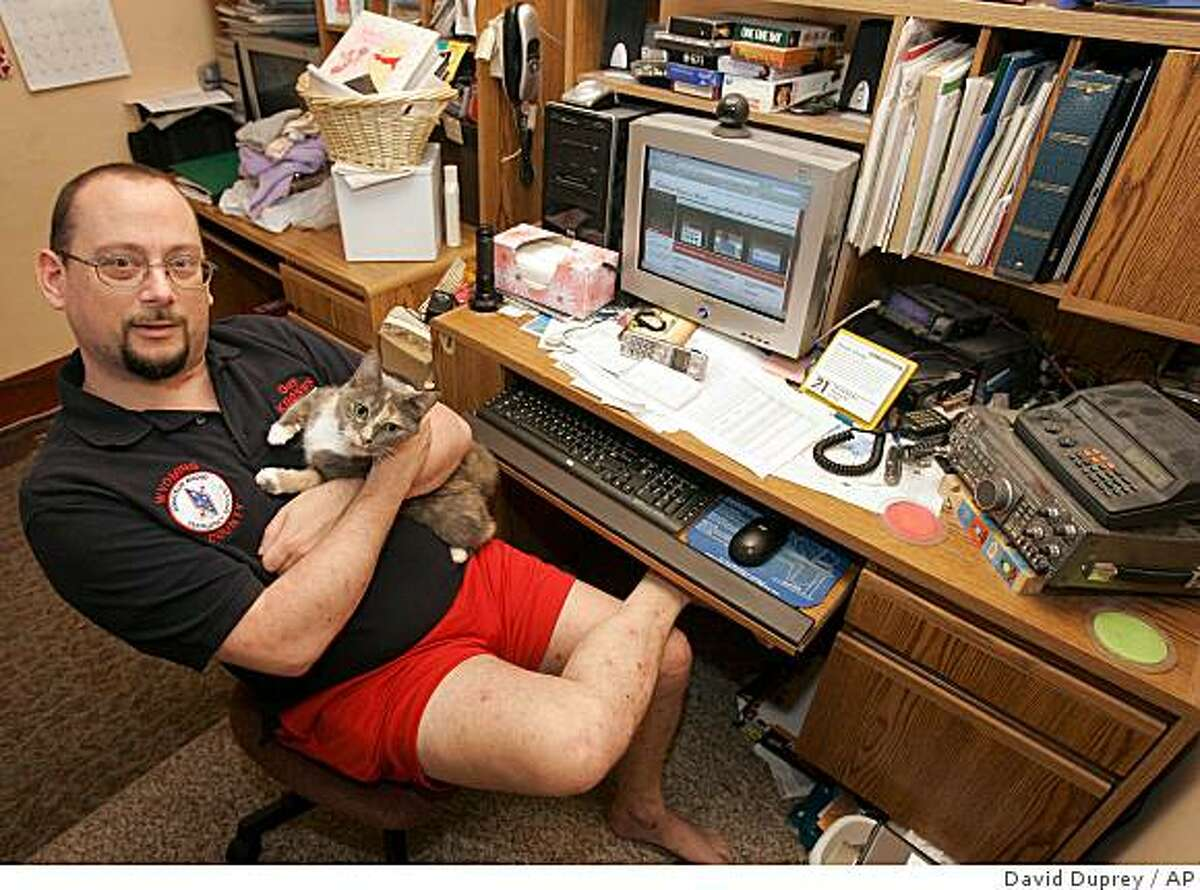 Guy Distaffen poses with his cat Patches in his computer room at his home in Silver Springs, N.Y., Thursday, Aug. 21, 2008. Three months ago, Distaffen switched Internet providers, lured from his cable company to his phone company by a year of free service on a two-year contract. But soon the company quietly updated its policies to say it would limit his amount of Internet activity each month. (AP Photo/David Duprey)