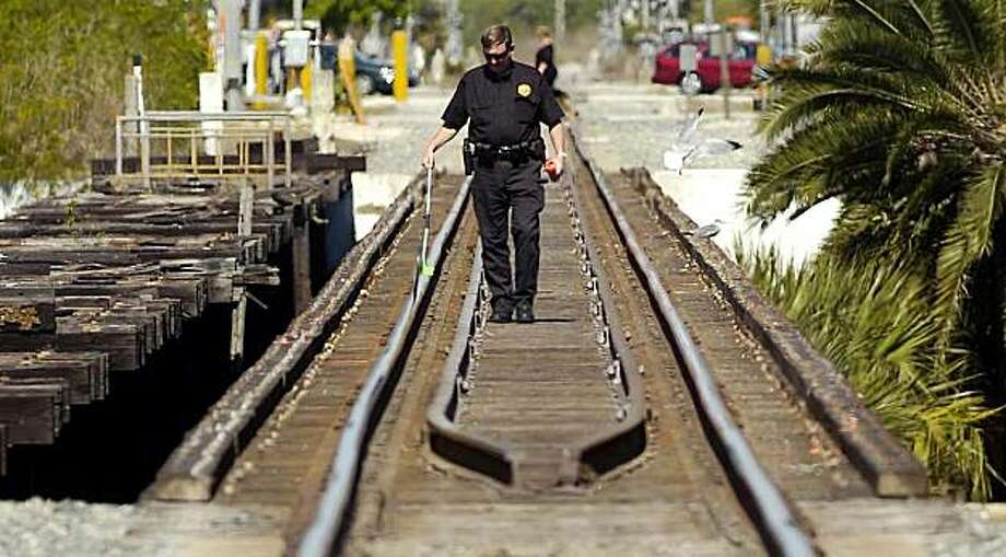 Mike Foremny, a Special Agent with the Railroad police, works the scene where three girls were struck and killed by a south bound train on the crane creek Railroad bridge in Melbourne, Fla., Sunday, Feb. 21, 2010. Photo: Craig Rubadoux, AP