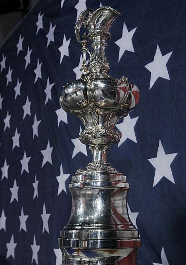 ** CORRECTS DATE ** Trophy The America's Cup  in front An American flag of the Stars and Stripes before a press conference held in Valencia, Spain on Monday 15 Feb, 2010.The America's Cup is poised to return to its traditional multiple challenger format.Oracle's trimaran beat Alinghi's catamaran. Photo: Alberto Saiz, AP