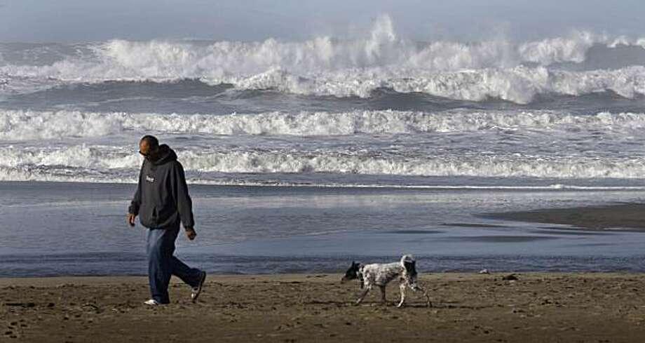 Evan Jones of San Francisco and his dog Kuro walk on Ocean Beach in San Francisco, Calif. on January 13, 2010. Photo: Lea Suzuki, The Chronicle