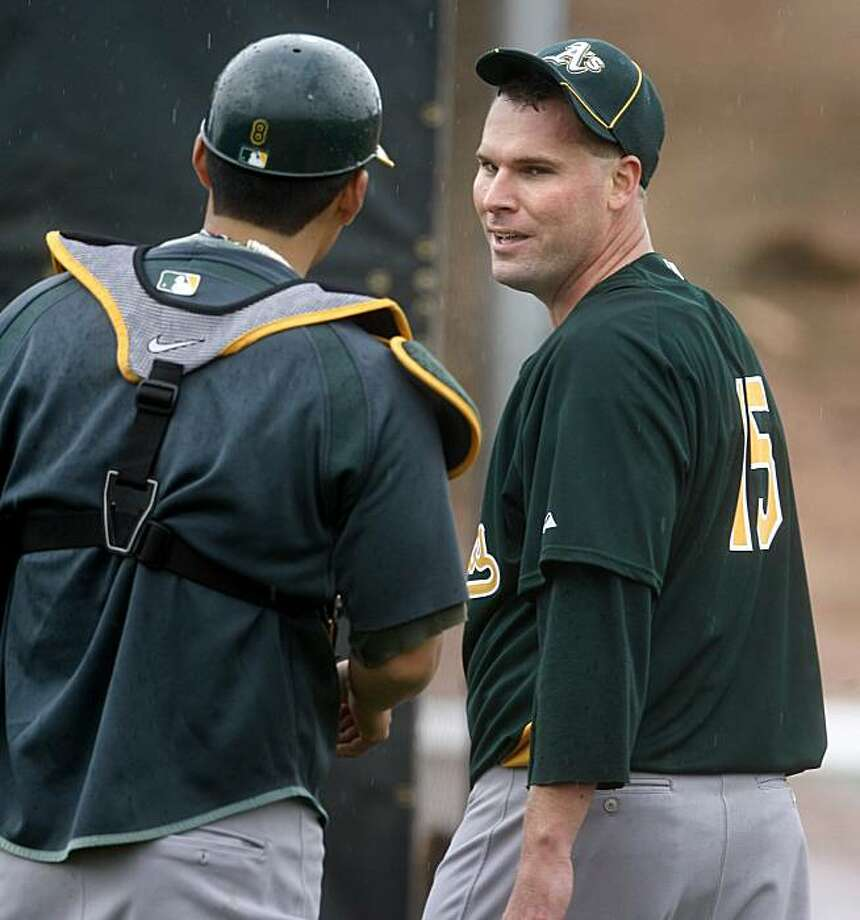 Oakland pitcher Ben Sheets, right, speaks with catcher Kurt Suzuki after throwing for the first time at spring training Sunday. Photo: Brant Ward, The Chronicle