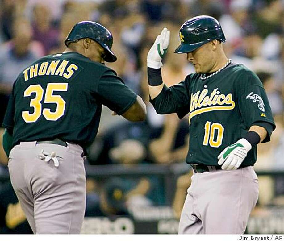 Oakland Athletics' Frank Thomas, left, greets Daric Barton at home plate after he hit a two-run home run against the Seattle Mariners' in the fourth inning of a baseball game in Seattle on Saturday, Aug. 23, 2008. (AP Photo/Jim Bryant) Photo: Jim Bryant, AP