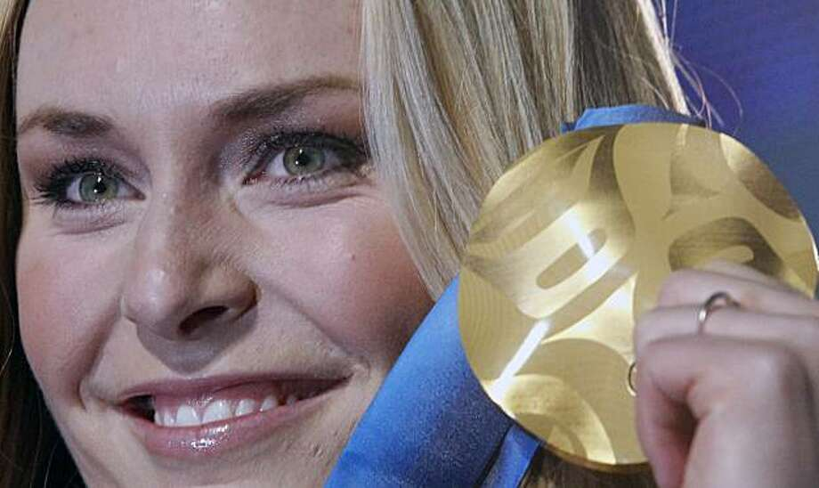 Lindsey Vonn of the United States, shows the gold medal she won in the Women's downhill, during the medal ceremony at the Vancouver 2010 Olympics in Whistler, British Columbia, Wednesday, Feb. 17, 2010. Photo: Luca Bruno, AP