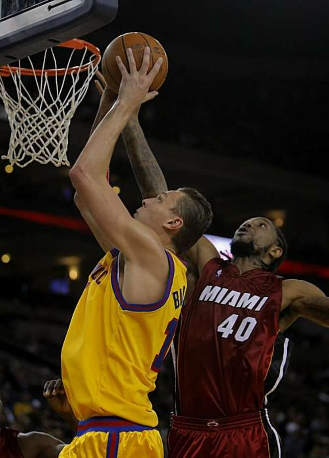 Andris Biedrins is fouled by Udonis Haslem while going up for a shot in the second half of play. The Golden State Warriors played the Miami Heat at Oakland-Alameda County Coliseum, in Oakland, Calif.,  on Wednesday, January 13, 2010. Photo: Carlos Avila Gonzalez, The Chronicle