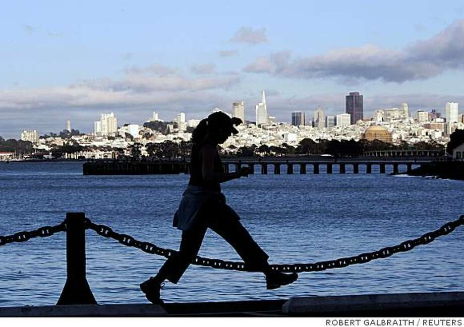 A woman runs along the shoreline of San Francisco Bay in San Francisco, California August 18, 2008.  REUTERS/Robert Galbraith (UNITED STATES) Photo: ROBERT GALBRAITH, REUTERS