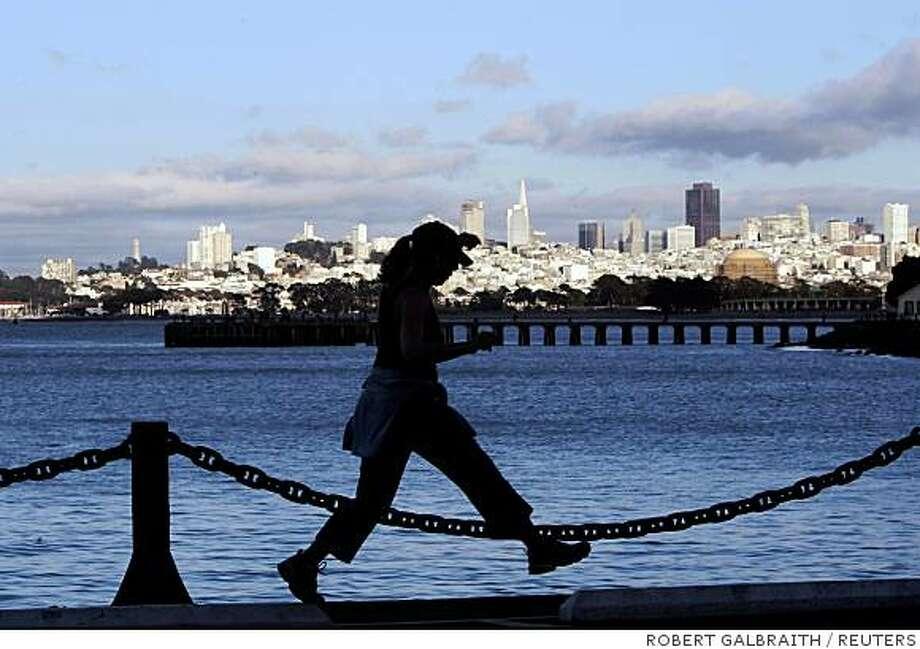 A woman runs along the shoreline of San Francisco Bay in San Francisco, California August 18, 2008.  REUTERS/Robert Galbraith (UNITED STATES) Photo: ROBERT GALBRAITH, REUTERS