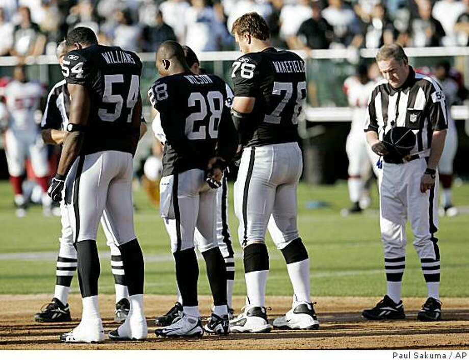 Oakland Raiders linebacker Sam Williams (54), safety Gibril Wilson (28) and Oakland Raiders offensive lineman Fred Wakefield (78) pause for a moment of silence honoring Oakland Raiders Hall of Fame guard Gene Upshaw before the Raiders preseason football game against the Arizona Cardinals in Oakland, Calif., Saturday, Aug. 23, 2008. Upshaw died earlier in the week.  (AP Photo/Paul Sakuma) Photo: Paul Sakuma, AP