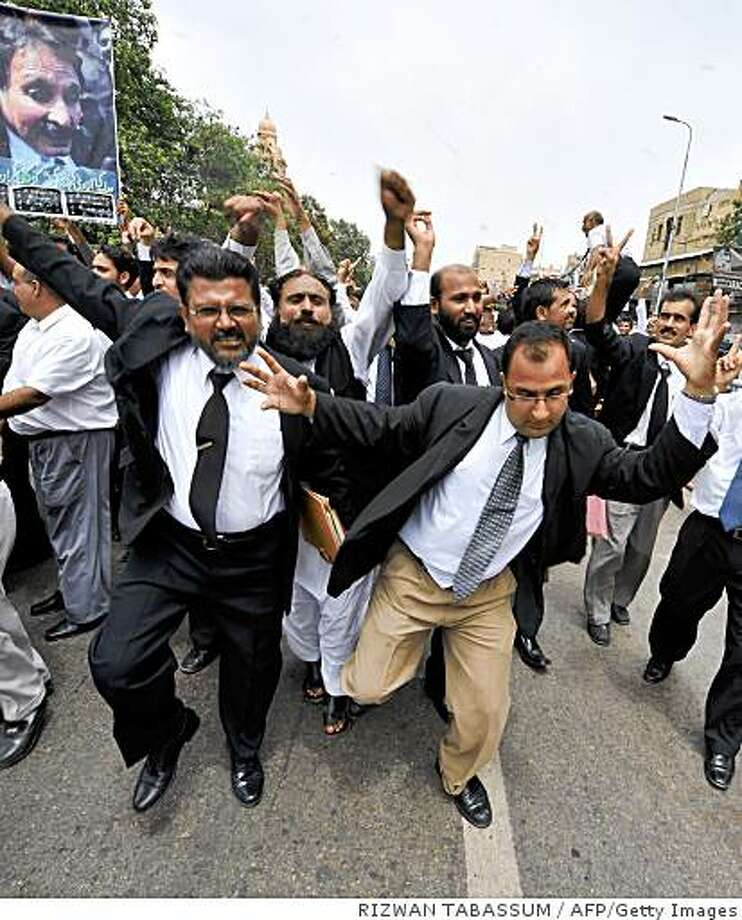 Pakistani lawyers celebrate the resignation of President Pervez Musharraf during a march on a street in Karachi on August 18, 2008. Musharraf announced his resignation on 18 August in the face of looming impeachment charges, ending a turbulent nine years in power for the key US ally. The former army chief, who seized power in a bloodless coup in 1999, had been under huge pressure to quit before the coalition government launched the first impeachment proceedings in Pakistan's 61-year history.   AFP PHOTO/Rizwan TABASSUM (Photo credit should read RIZWAN TABASSUM/AFP/Getty Images) Photo: RIZWAN TABASSUM, AFP/Getty Images