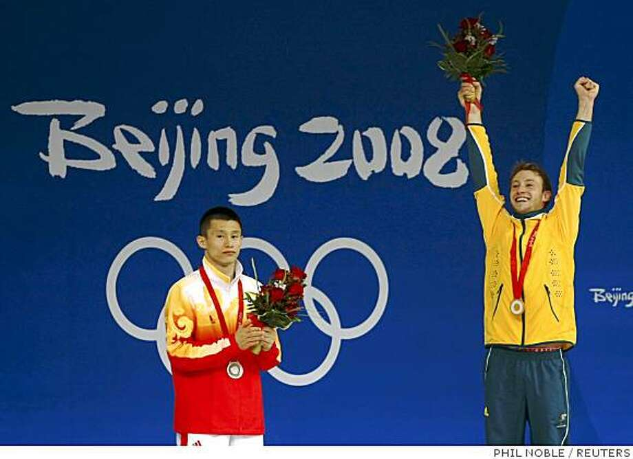 Gold medallist Matthew Mitcham (R) of Australia celebrates on the podium next to silver medallist Zhou Luxin of China after the men's 10m platform diving final at the Beijing 2008 Olympic Games August 23, 2008.     REUTERS/Phil Noble (CHINA) Photo: PHIL NOBLE, REUTERS