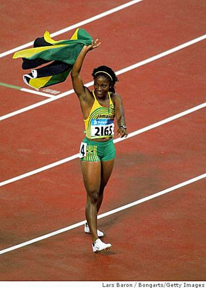 BEIJING - AUGUST 17:  Shelly-Ann Fraser (R) of Jamaica celebrates winning the Women's 100m Final and the gold medal held at the National Stadium on Day 9 of the Beijing 2008 Olympic Games on August 17, 2008 in Beijing, China.  Shelly-Ann Fraser of Jamaica finished the event in first place with a time of 10.78.  (Photo by Lars Baron/Bongarts/Getty Images) Photo: Bongarts/Getty Images