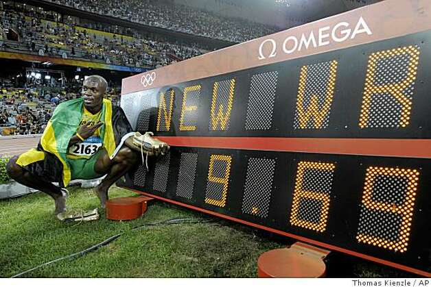 Jamaica's Usain Bolt poses next to the scoreboard after setting a new world record as he wins the gold medal in the men's 100-meter final in the National Stadium  at the Beijing 2008 Olympics in Beijing, Saturday, Aug. 16, 2008. Photo: Thomas Kienzle, AP