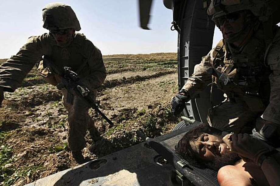 During a sporadic firefight, U.S. Marines guard a wounded and combative Taliban fighter, one of two captured minutes earlier, according to witnesses, during a U.S. Army Task Force Pegasus medevac mission, in Marjah, Helmand province, Afghanistan, Wednesday Feb. 17, 2010. The two were transported to a nearby U.S. Navy field hospital. Pegasus aeromedical crews have been attacked regularly over the past days while evacuating the wounded as U.S. and Afghan troops take part in an assault in the Taliban stronghold of Marjah. Photo: Brennan Linsley, AP