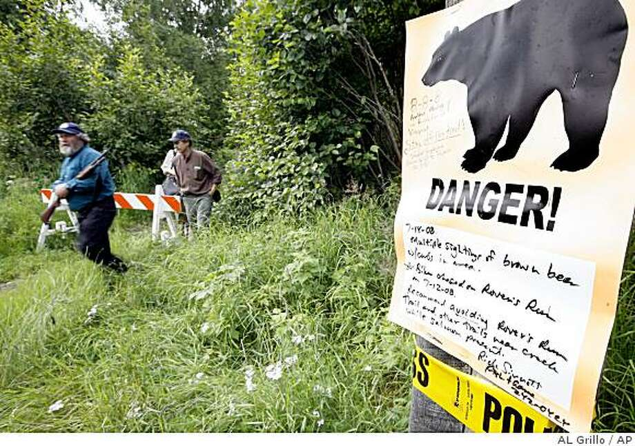 Alaska Fish and Game biologists Sean Farley, left, and Rick Sinnott walk past a warning sign as they look for a bear alone a path Far North Bicentennial Park in Anchorage, Alaska on Wednesday Aug. 13, 2008, where a jogger and a bicyclist were attacked by a sow with two cubs this summer.  The attacks happened on wilderness trails shared by humans and bears. (AP Photo/Al Grillo) Photo: AL Grillo, AP