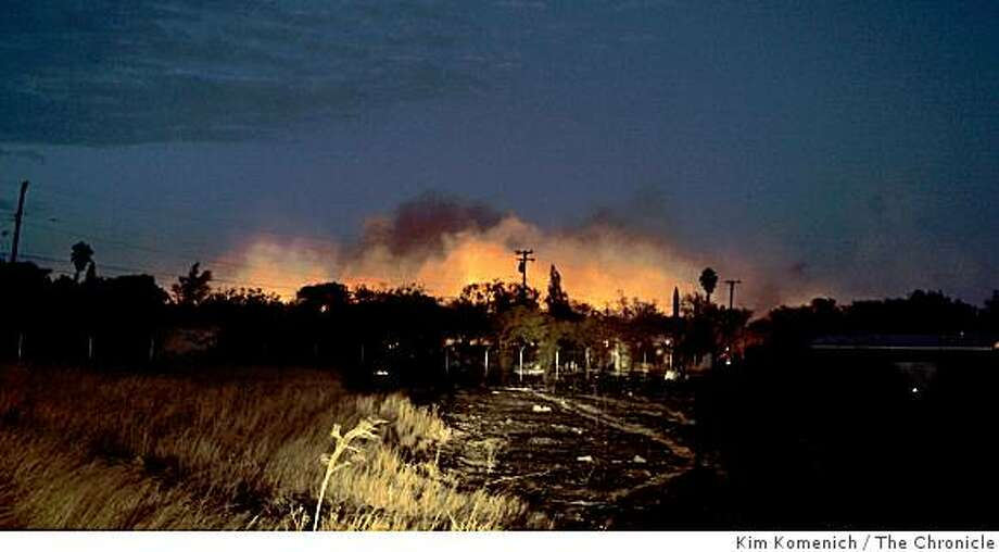 The sky is aglow as seen from just outside the main gate at Travis Air Force base as a wind-driven fire consumes about 40 structures on the base on Saturday, August 16, 2008. The buildings were scheduled for demolition and were not inhabited. Photo: Kim Komenich, The Chronicle