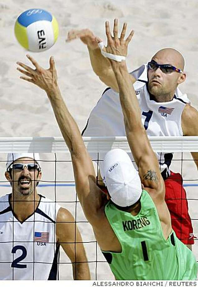 Todd Rogers (L) of the U.S. looks on while teammate Philip Dalhausser (R) hits the  ball as Eric Koreng of Germany defends during their men's beach volleyball quarterfinal match at the Beijing 2008 Olympic Games, August 18, 2008.   REUTERS/Alessandro Bianchi (CHINA) Photo: ALESSANDRO BIANCHI, REUTERS