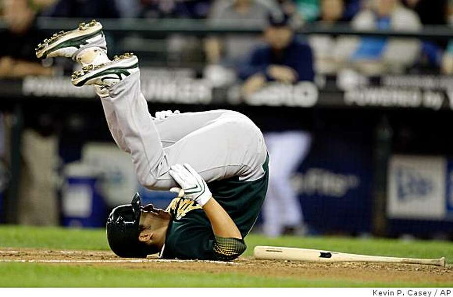 Oakland Athletics' Kurt Suzuki rolls on the ground after being hit by a pitch thrown by Seattle Mariners' pitcher Sean Green in the sixth inning of a baseball game in Seattle on Friday, Aug. 22, 2008. (AP Photo/Kevin P. Casey) Photo: Kevin P. Casey, AP