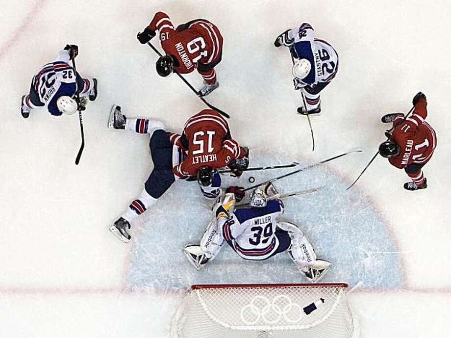 USA goalie Ryan Miller makes a save on Canada's Ryan Getzlaf (51) during the frantic last few minutes of the USA's 5-3 victory in men's hockey preliminary round action at the 2010 Winter Olympics on Sunday, Feb. 21, 2010, in Vancouver. ( Smiley N. Pool / Houston Chronicle) Photo: Smiley N. Pool, Chronicle Olympic Bureau
