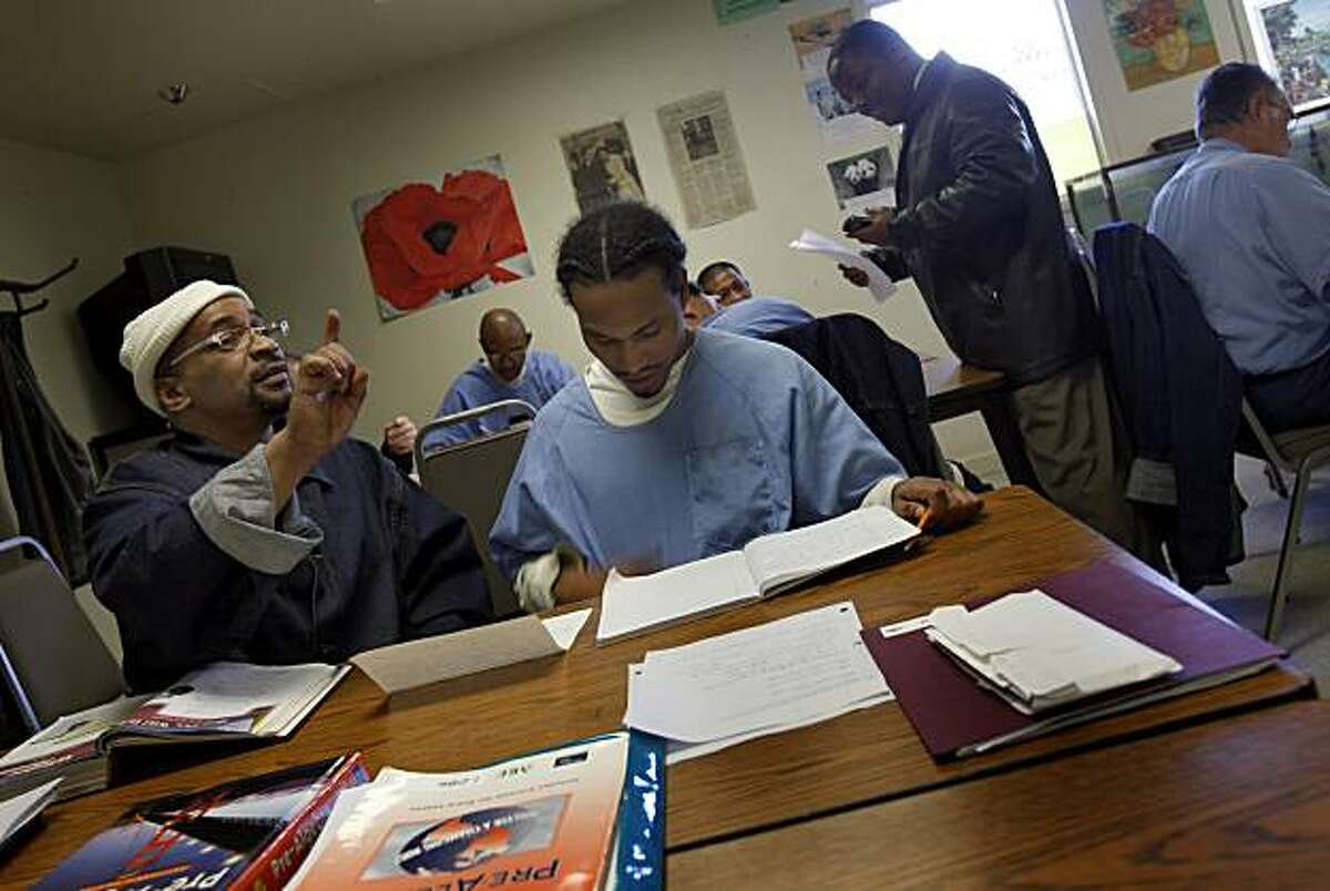 Inmate Derrick Cooper (left) posed a question while he and Dominique Oden did papers in their adult basic education class Tuesday February 9, 2010, one of the educational opportunities at the prison. A new California law aimed at cutting prison spending includes the cutting of education and vocational spending at San Quentin (Marin County) and other state prisons.
