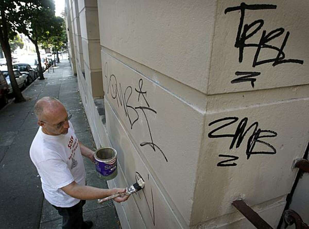 Parishoner Robert Pritchard paints over graffiti tagged on the Fell Street side of Sacred Heart Catholic Church in San Francisco, Calif., on Saturday, Aug. 8, 2009. Pritchard has become the unofficial caretaker of the aging building was closed in 2005. Graffiti has become such a huge problem that Pritchard makes weekly visits to paint over the markings.