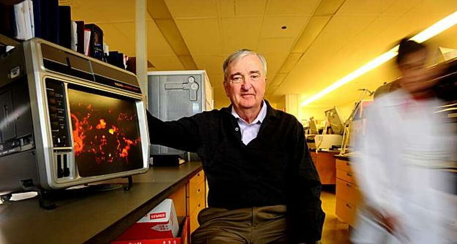 Dr. Larry Drew poses in a University of California, San Francisco laboratory on Friday, Feb. 12, 2010, in San Francisco. At left is an image of respiratory cells infected with a virus. Photo: Noah Berger, Special To The Chronicle