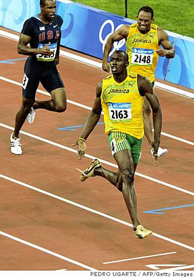 """Jamaica's Usain Bolt (front) reacts after winning the men's 100m final at the """"Bird's Nest"""" National Stadium as part of the 2008 Beijing Olympic Games on August 16, 2008. Jamaica's Usain Bolt won the Olympic Games men's 100m gold medal in a new world record time of 9.69sec. Trinidad and Tobago's Richard Thompson (9.89sec) and Walter Dix of the US (9.91) took silver and bronze respectively.   AFP PHOTO / PEDRO UGARTE (Photo credit should read PEDRO UGARTE/AFP/Getty Images) Photo: PEDRO UGARTE, AFP/Getty Images"""