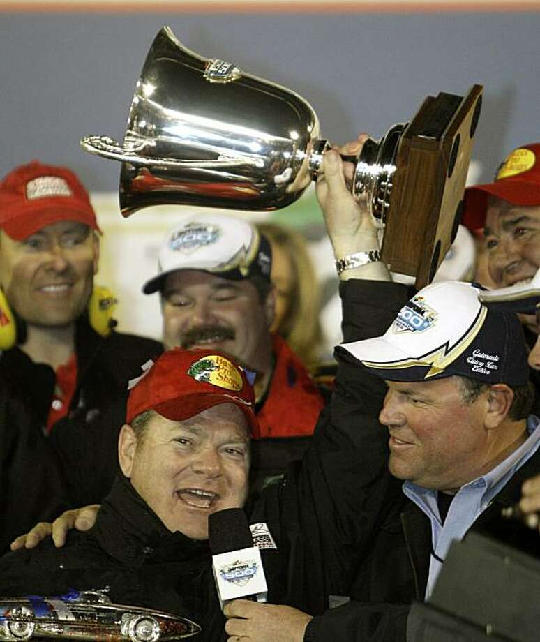 In this photo taken Feb. 14, 2010, Team owner Chip Ganassi, left, holds up the owners trophy while being interviewed by Daytona International Speedway President Robin Braig after driver Jamie McMurray won the Daytona 500 NASCAR auto race at Daytona International Speedway in Daytona Beach, Fla. Photo: John Raoux, AP