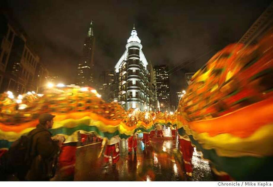With a giant lit dragon in tow, the White Crane Kung Fu group past the city skyline during their last stop on the Chinese New Year on Saturday, Feb. 23, 2008 in San Francisco, Calif. Photo by Mike Kepka / San Francisco Chronicle Photo: Mike Kepka