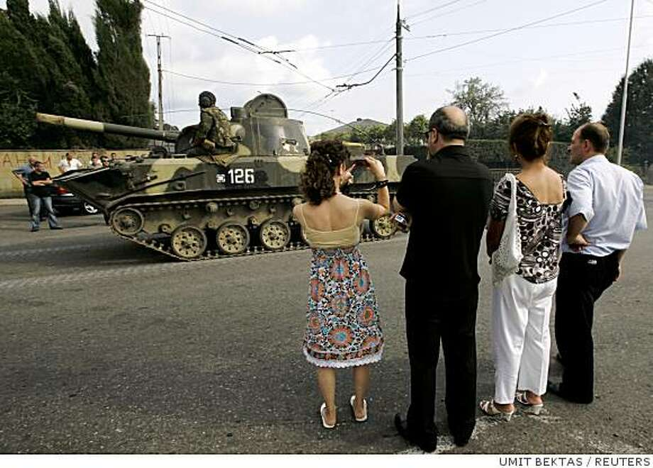Georgians watch as a Russian military convoy leaves Georgia in the western Georgian city of Zugdidi August 22, 2008. A column of about 150 Russian military vehicles left Georgia proper on Friday and pulled back into the breakaway region of Abkhazia on the Black Sea, a Reuters cameraman said.   REUTERS/Umit Bektas (GEORGIA) Photo: UMIT BEKTAS, REUTERS