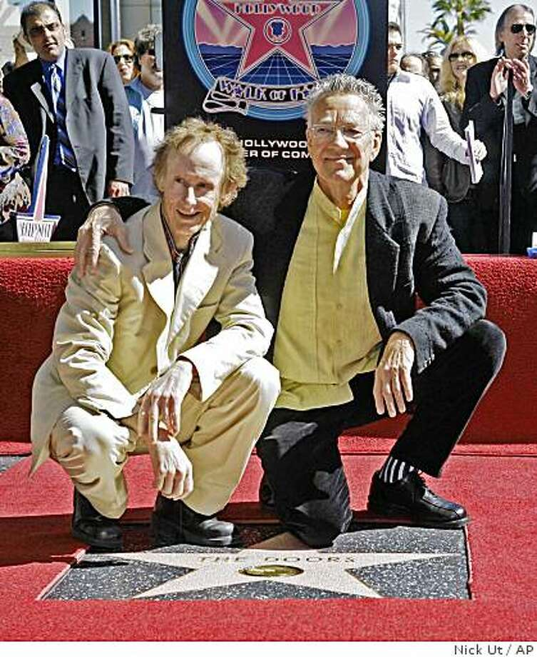 The Doors' keyboardist Ray Manzarek, right, and guitarist Robby Krieger, pose in this Wednesday, Feb. 28, 2007 file photo, on the Hollywood Walk of Fame in Los Angeles. The end is near for a bitter legal dispute between the three surviving members of The Doors now that the California Supreme Court has refused to take up their case on Aug. 13, 2008. Keyboardist Ray Manzarek and guitarist Robby Krieger are on the hook for more than $5 million after they were found by lower courts to have improperly invoked The Doors' name and images during a 2003 concert tour. After the high court declined to hear their appeal they'll have to pay up to drummer John Densmore, the parents of the deceased lead singer Jim Morrison and the parents of Morrison's deceased wife, Pamela Courson, who died in 1974. Photo: Nick Ut, AP