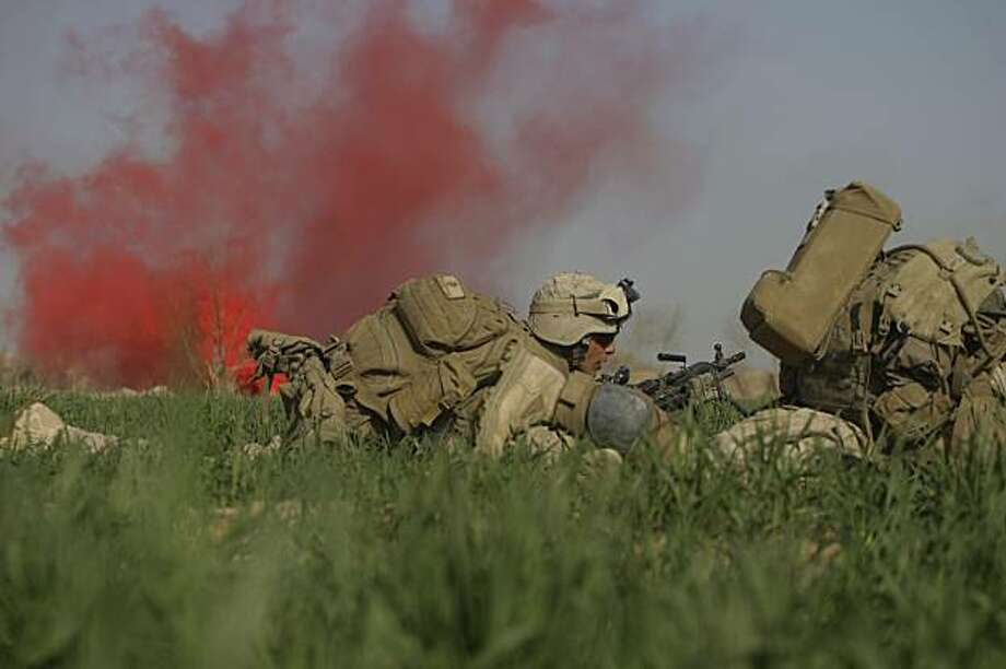 U.S. Marines from 3rd Battalion, 6th Marine Regiment take cover in an open poppy field during a firefight as Taliban fighters fire on them in the town of Marjah in Afghanistan's Helmand province on Monday Feb. 15, 2010. Photo: David Guttenfelder, AP
