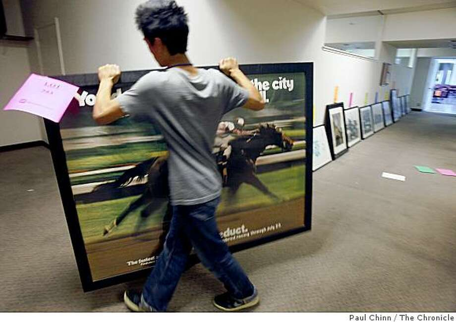 Phillip Ma organizes framed photographs for this weekend's auction at Bay Meadows Race Track in San Mateo, Calif., on Thursday, Aug. 21, 2008. Photo: Paul Chinn, The Chronicle