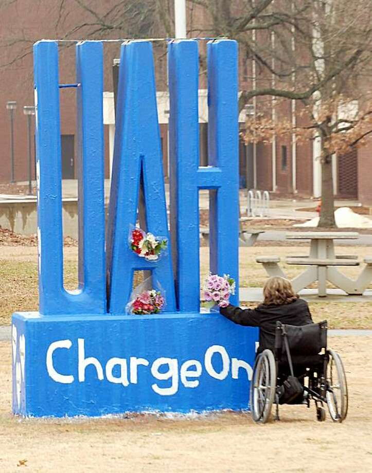 Kristina Liddle, a junior at UAH, leaves a bouquet of flowers at a UAH monument next to the University Center where a service was held to mourn the three faculty slain, and three others wounded last last Friday during a shooting at University of Alabama in Huntsville, Ala., Sunday, Feb. 14, 2010. Photo: Dave Dieter, AP