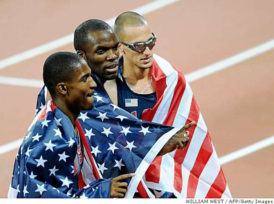 US athletes Lashawn Merritt (C), Jeremy Wariner (R) and David Neville, wrapped in their national flag, celebrate winning respectively gold, silver and bronze in the men's 400m final at the National stadium as part of the 2008 Beijing Olympic Games on August 21, 2008. Lashawn Merritt of the US won ahead of fellow countrymen Jeremy Wariner and David Neville.            AFP PHOTO / WILLIAM WEST (Photo credit should read WILLIAM WEST/AFP/Getty Images) Photo: WILLIAM WEST, AFP/Getty Images