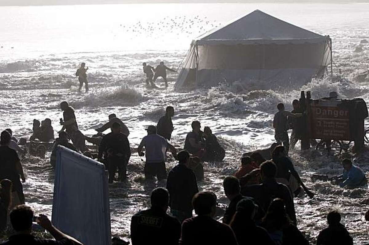 Bystanders scramble as rogue wave washes over the beach during the Mavericks Surfing Contest on Saturday Feb. 13, 2010 in Pillar Point, Calif. Several injuries where reported. All non-emergency personal was evacuated from the beach.