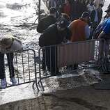 People climb protective barriers as  a rogue wave washes over the beach during the Mavericks Surfing Contest on Saturday Feb. 13, 2010 in Pillar Point, Calif.  Several injuries where reported. All non-emergency personal was evacuated from the beach.