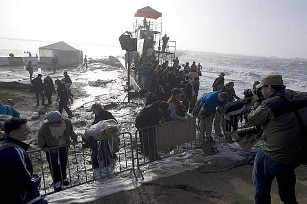 People climb protective barriers as  a rogue wave washes over the beach during the Mavericks Surfing Contest on Saturday Feb. 13, 2010 in Pillar Point, Calif.  Several injuries where reported. All non-emergency personal was evacuated from the beach. Photo: Chad Ziemendorf, For The Chronicle