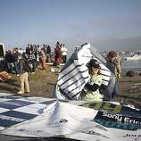 A Mavericks staff members picks up the contestants list after after a rogue wave wash of the beach during the Mavericks Surfing Contest on Saturday Feb. 13, 2010 in Pillar Point, Calif.  Several injuries where reported. All non-emergency personal was evacuated from the beach.
