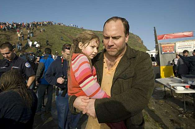 "Vince Perrini and carries his daughter Sofia Perrini after being pulled under when a rogue waves washed over the beach during the Mavericks Surfing Contest on Saturday Feb. 13, 2010 in Pillar Point, Calif.  Several injuries where reported. All non-emergency personal was evacuated from the beach. ""We both go pulled under and it was pretty scary,"" said Perrini. Photo: Chad Ziemendorf, For The Chronicle"