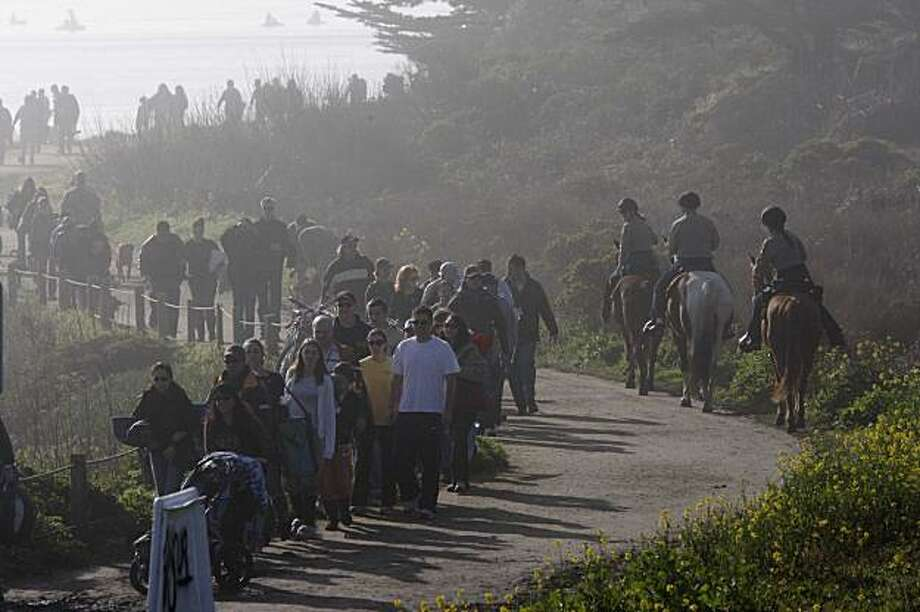 Surfing enthusiasts evacuate the beach after rouge waves overtook the beach area where people were watching the Mavericks Surf Contest on Saturday Feb. 13, 2009 in Pillar Point, Calif.  Several people were injured and everybody was told to leave. Photo: Mike Kepka, The Chronicle