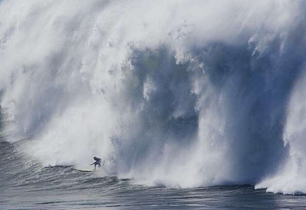 A surfer barely hangs on before a crashing wave catches up with him during the semifinals of the Mavericks Surf Contest in Half Moon Bay on Saturday. Photo: Adam Lau, The Chronicle