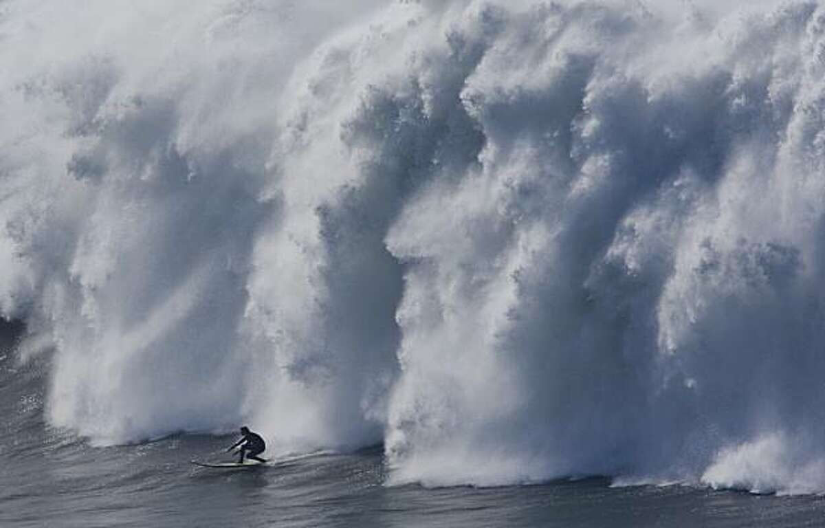 A surfer coasts in front of crashing waves during the seminfinals of the Mavericks Surf Contest in Half Moon Bay on Saturday.