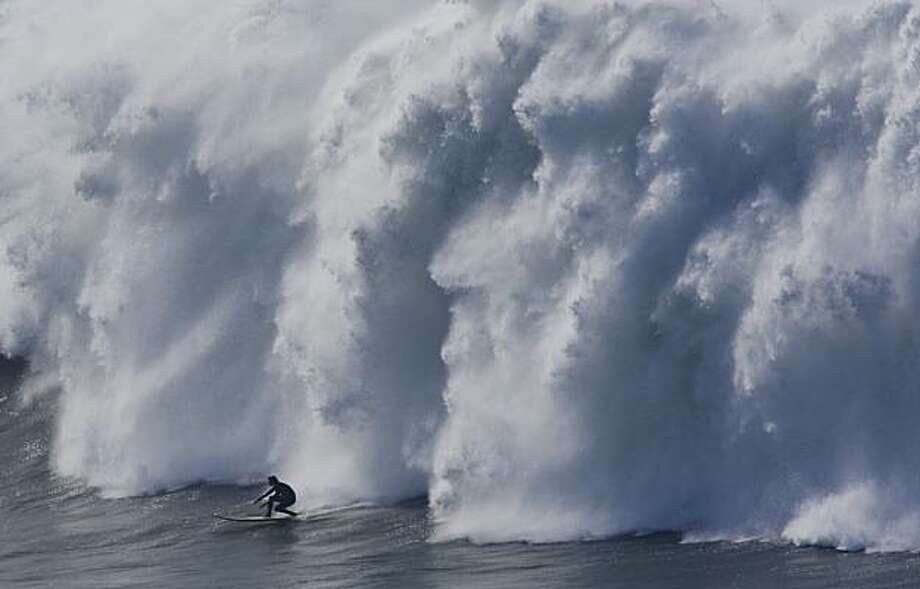 A surfer coasts in front of crashing waves during the seminfinals of the Mavericks Surf Contest in Half Moon Bay on Saturday. Photo: Adam Lau, The Chronicle